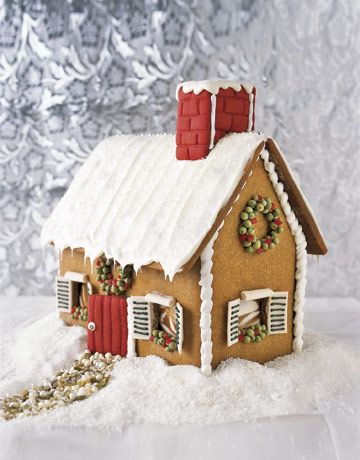 gingerbread house with red chimney and door with snowy background