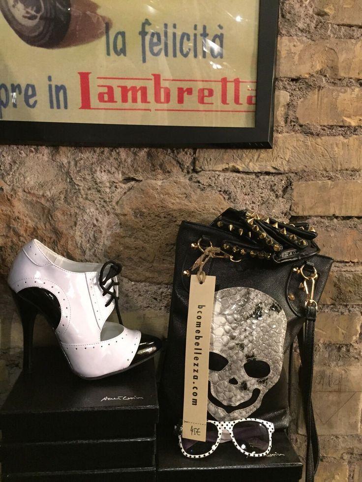 Outfit composto da scarpe bianche e nere, occhiali vintage bianchi a pois, e borsa nera con borchie color oro e teschio.