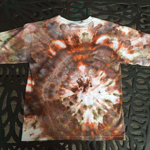 This is a vibrant hand-dyed t-shirt for youths and teens reminiscent of a camo spiral! Use your imagination to find interesting images in the design. This one of a kind ice dyed item is unique and a great gift for one of the young ones in your life! Colour- Brown, Green, Orange Size- Medium Youth (10-12) Brand- M&O Youth  To create this artistic design ice is used to deposit professional quality dye onto the fabric and the abstract art is created over a period of 24 hours. This item has…