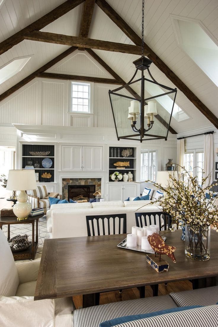 A gorgeous white paint job unites the kitchen, dining room and great room, while high ceilings and rustic antique beams show off the home's bright, open quality.