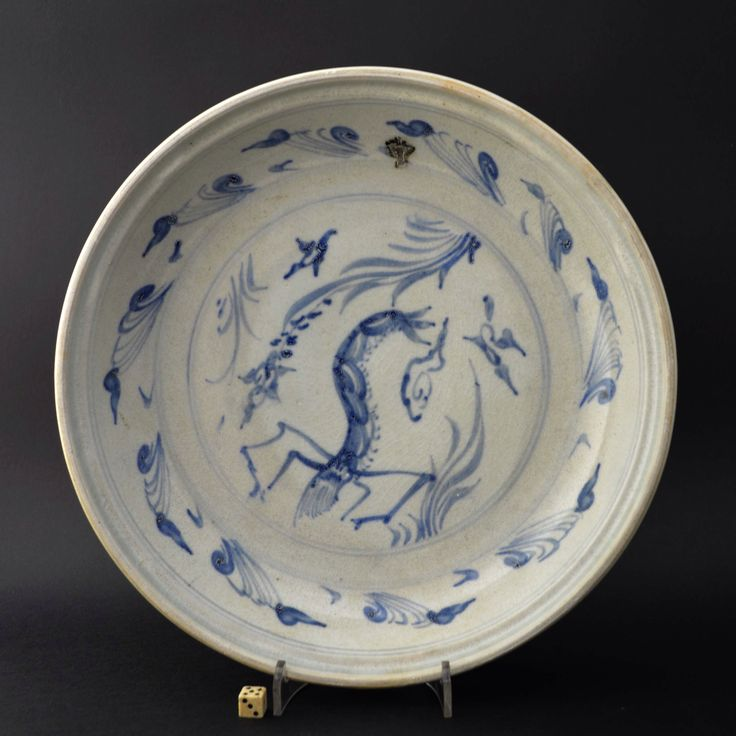 A rare 15th Century Vietnamese pottery dish from the Hoi An Shipwreck. Decorated in Blue and White with a prawn among aquatic plants. There were very few dishes decorated with prawns on the Hoi An Hoard Shipwreck. The rim of the dish has the glaze wiped clean to expose the biscuit body. This was done because these moulded dishes were fired face to face, so the unglazed rims would touch one another in the Kiln, had there been Glaze on the Rims they would has become stuck together.