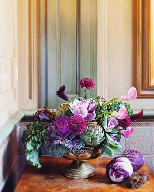 A striking color palette of plum and magenta florals complement the  purples in cabbages and flowering kale to make a cohesive and interesting fall centerpiece. Visit our site {link in profile} for more of our favorite autumn arrangements! Styling: @e_kathleenvarner . . . #fall #autumn #floral #florals #flowers #arrangement #centerpiece #dahlia #callalily #kale #cabbage #artichoke #stilllife #color #texture #purple #green