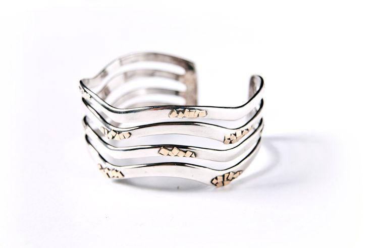 Il bracciale si ispira alle onde del mare in argento, con gli spruzzi realizzati con frammenti d'oro.