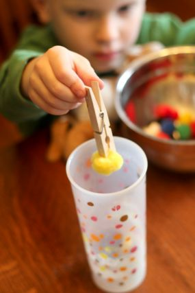 Build fine motor skills by transferring pom poms with clothes pins.