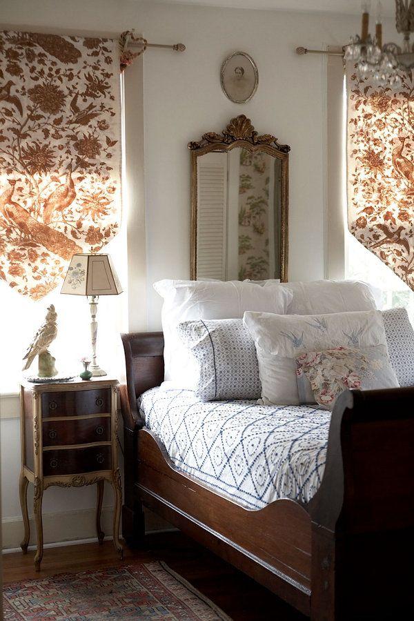 Vintage cottage bedroom.  Dark wood sleigh bed, nightstand, long gold mirror, hardwood floor, chandelier