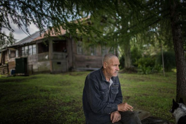 Vasily Rasskazov, the only man living in the village of Vorobyovo, sits nearby the Sukhona River, July 2015.  A former farmer now retired, Rasskazov visits often his friend who lives in the nearby Nizhny Pochinok village. Rasskazov expresses disappointment with USSR, which he blames for the disappearance of small villages, and he greets Putin's policy on foreign affairs.