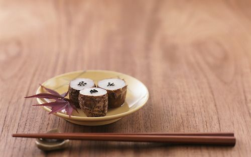 wood backdrop, wood chopsticks. minimal comp with small plate of sushi. rustic feel.
