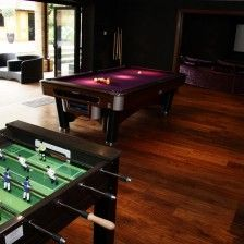 A luxury games room in Hertfordshire showcasing a bespoke copper pool table and a table football.