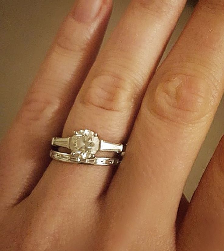 Engagement ring with round brilliant cut diamond and tapered baguettes, sitting next to a platinum diamond wedding ring, channel set with baguette diamonds.