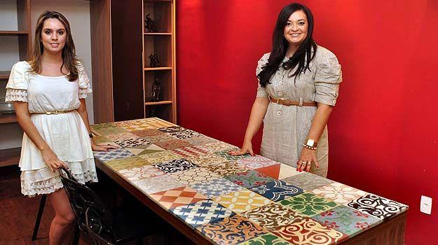 Ívia Maia e Mirlene Saels mostram mesa de madeira de tampo refeito com azulejos antigos (Eduardo de Almeida/RA studio)