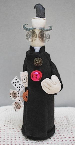 Amos é um ilusionista steampunk com olhos hipnóticos. Como todo bom mágico, tem sempre à sua disposição um baralho e um globo flutuante. Amos é 100% feito à mão, e tem cerca de 23cm de altura e 10cm em sua parte mais larga. R$80,00