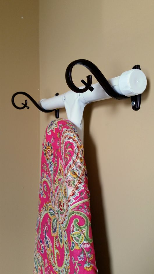 Think outside the box--use curtain rod brackets to hang an ironing board. #laundryroom #organization #ironingboardideas
