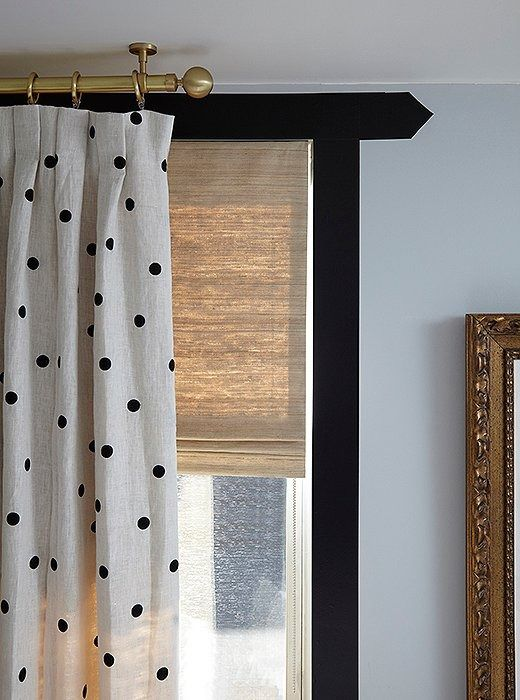 A pair of custom roman blinds from The Shade Store in the same solid silk fabric used for the outside of the canopy bed's drapes help tie the room together—and flood it with natural light.