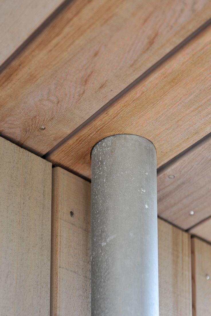 Zinken regenpijp netjes afgewerkt in het (red cedar)houten plafond.