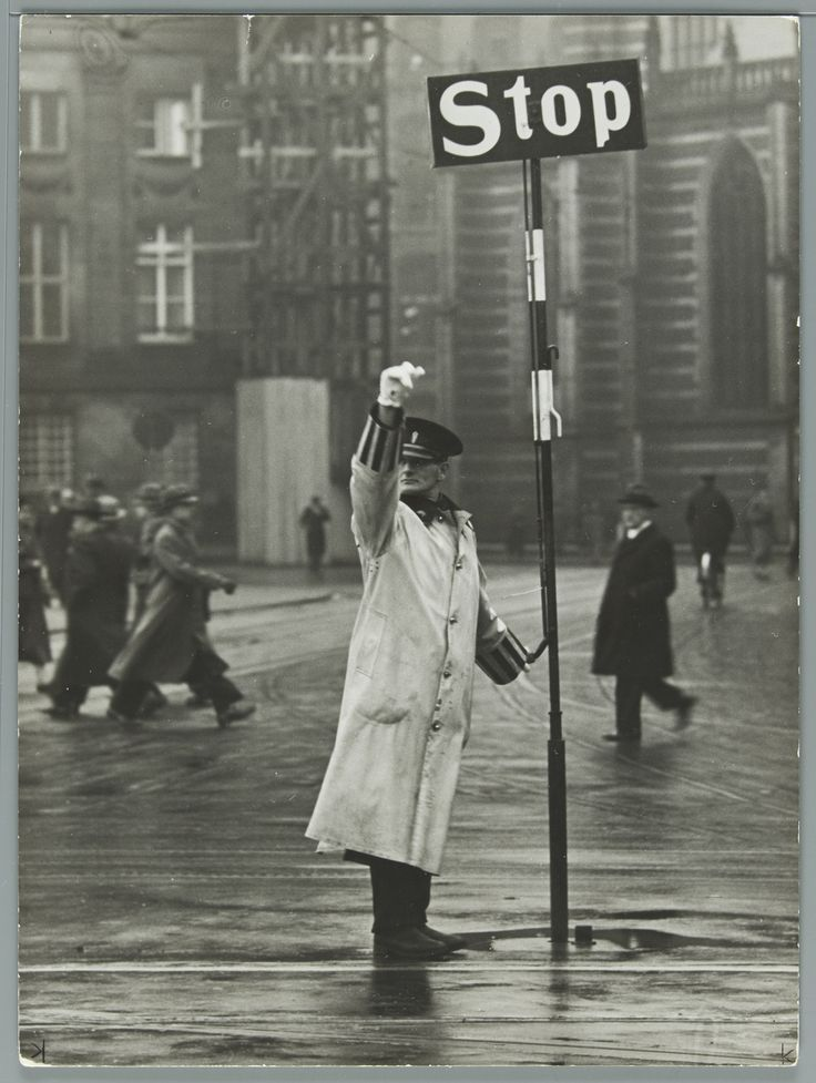 Verkeersagent bij stopbord regelt het verkeer in Amsterdam, volgens mij ergens op de Dam.