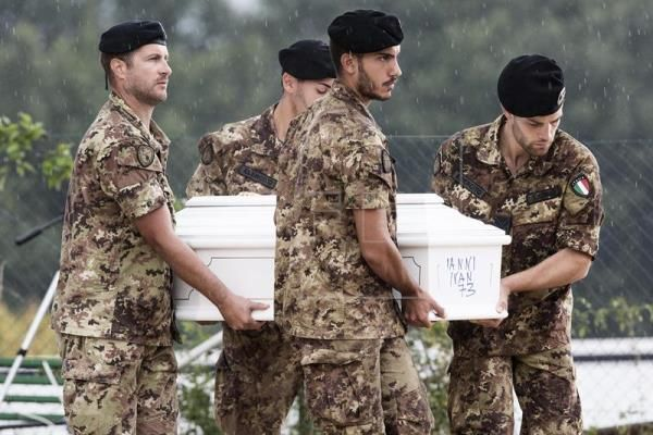 Italian soldiers carry a coffin as they prepare for a funeral.  EPA/ROBERTO SALOMONE