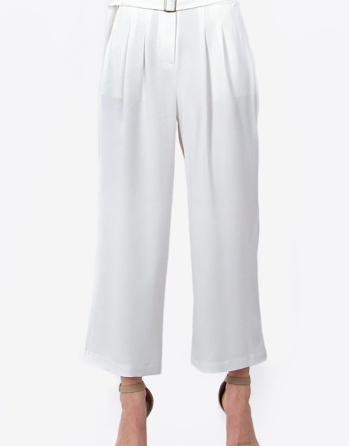 Look classy and chic in these white wide leg trousers. Pair it with a white strapless crop top and nude heels for a chic minimal ensemble.  – White wide leg pants – Belted – Zipper closure – Side pockets  Size + Fit – Model is wearing size S – Measurements taken from size S – Waist: 28″