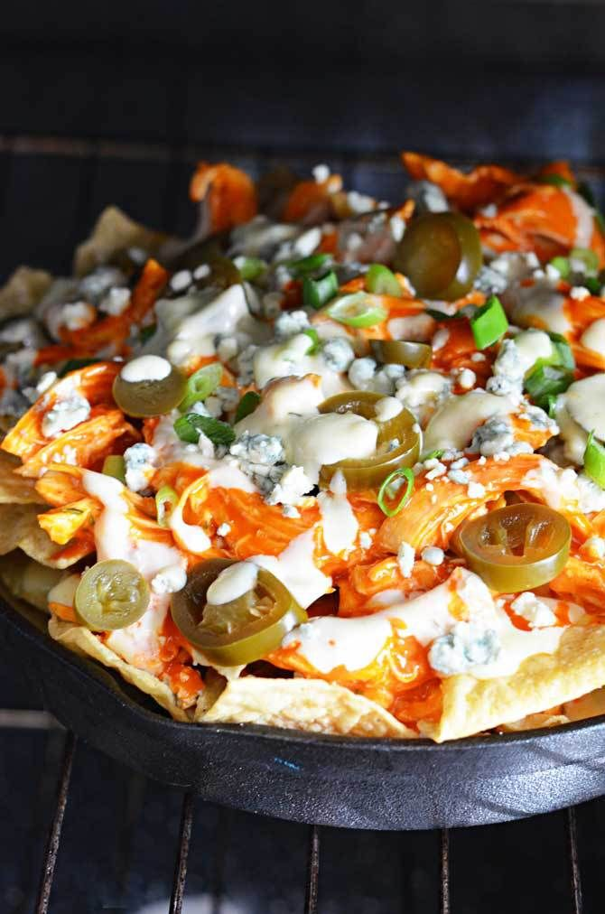 Loaded Buffalo Chicken Nachos.  Could this be any more perfect for football season?  Shredded buffalo chicken, cheesy ranch queso, blue cheese crumbles, pickled jalapenos, and chopped green onions!  The ultimate appetizer!   hostthetoast.com