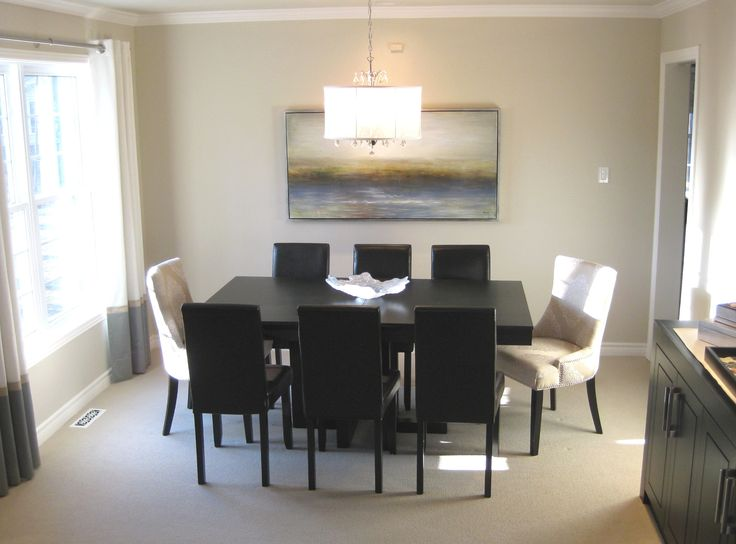 This sun filled dining room has a touch of the seaside dressed in sandy colours, soft blues and a touch of white. The oversized harmony artwork draws the eye into the sea. The upholstered chairs breaks up the hard lines of this modern dining set.