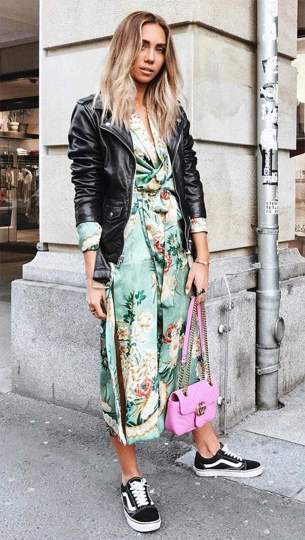 Lisa Olsson usa vestido floral midi, jaqueta de couro, vans e bolsa pink.