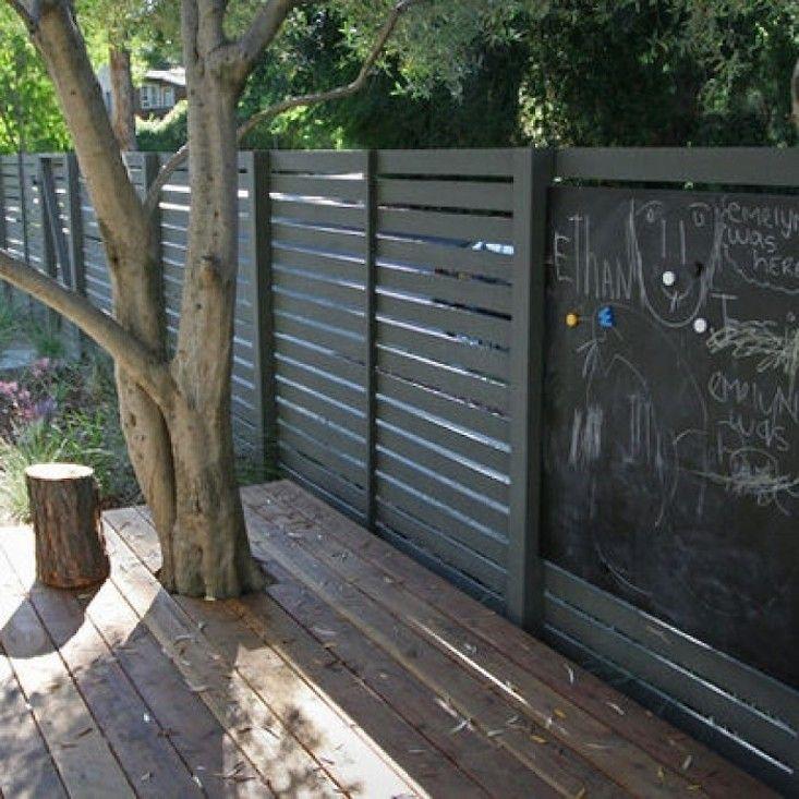 Black horizontal slat fence with a chalkboard element. Brilliant idea! Gardenista.
