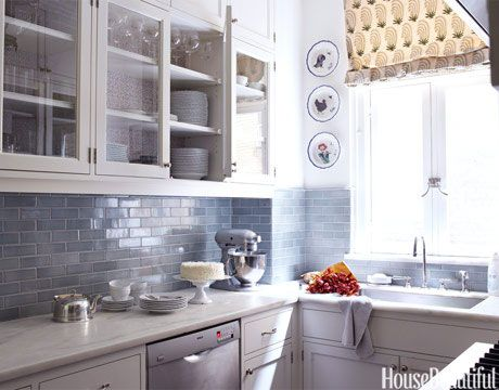 A backsplash of blue-gray Metro subway tile is paired with white cabinets in this small but distinctive Park Avenue kitchen.