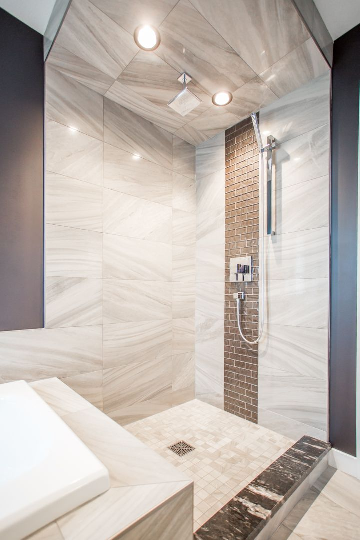 Custom tile shower with accent strip and granite step.