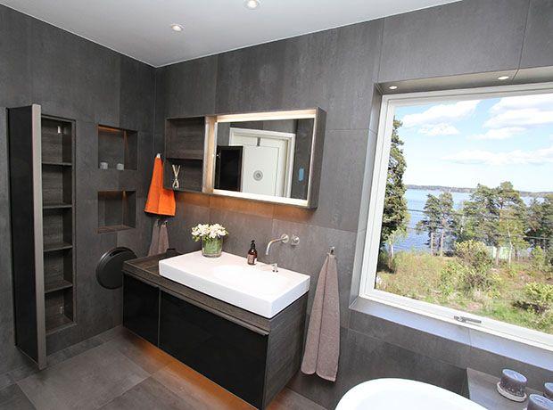 Ett exklusivt badrum i gråskala. Väggar som golv är täckta av stora skifferplattor. Det stora badkaret i lyxig design har inbyggd blandare och är placerat framför det stora fönstret med sjöutsikt. I väggarna finns flera belysta nischer som fungerar perfekt för förvaring av handdukar och andra badrumsartiklar. Det stora vägghängda handfatet i unik design är placerat på en skiva av svart granit.