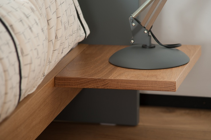 A Close Up Of The Bedside Table Attached To The Headboard