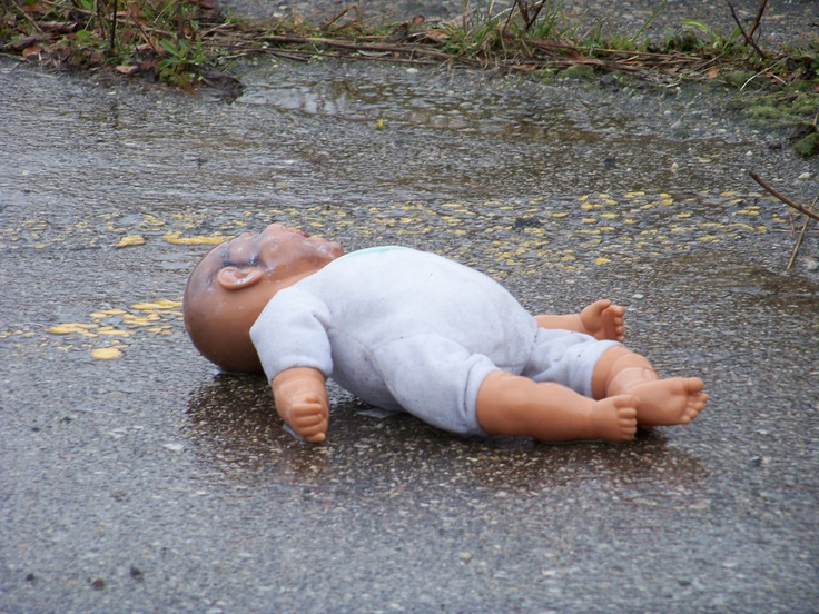 Abandoned doll in an abandoned hospital parking lot.