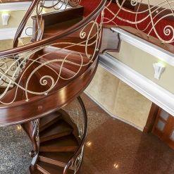 www.trabczynski.com ST433 Spiralne schody gięte z podstopniami, wykonane z barwionego mahoniu sapelli. Bogato zdobione policzki. Ręcznie kute stalowe balustrady z pochwytami drewnianymi. Realizacja wykonana w prywatnej rezydencji , projekt – Robert Kiona & TRABCZYNSKI
