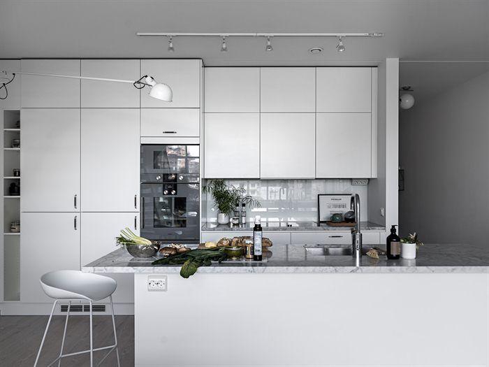 Istället för kakel täcks väggen vid arbetsytan av ett stänkskydd i vitt glas. Här finns gott om förvaring i flera praktiska skåp och kökslådor   Ballingslöv
