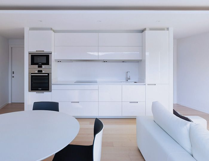 SANTOS kitchen. House type: Terraced house.  Kitchen distribution: Linear. Model: Gloss White MINOS-L.In order to have an ample day area the kitchen, dining and sitting room were joined to form one area.