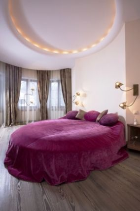 romantic bedroom with round bed and purple covering
