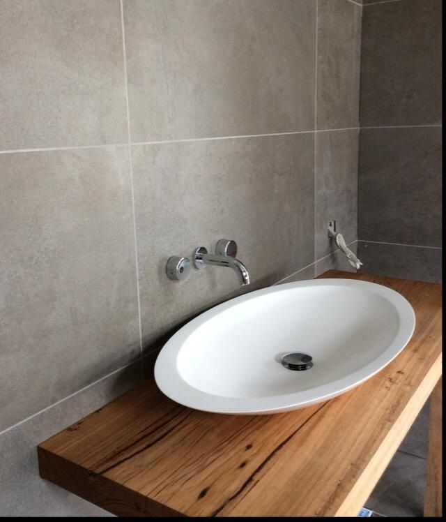 Light grey wall & floor tiles | timber vanity top | white basin and cupboards