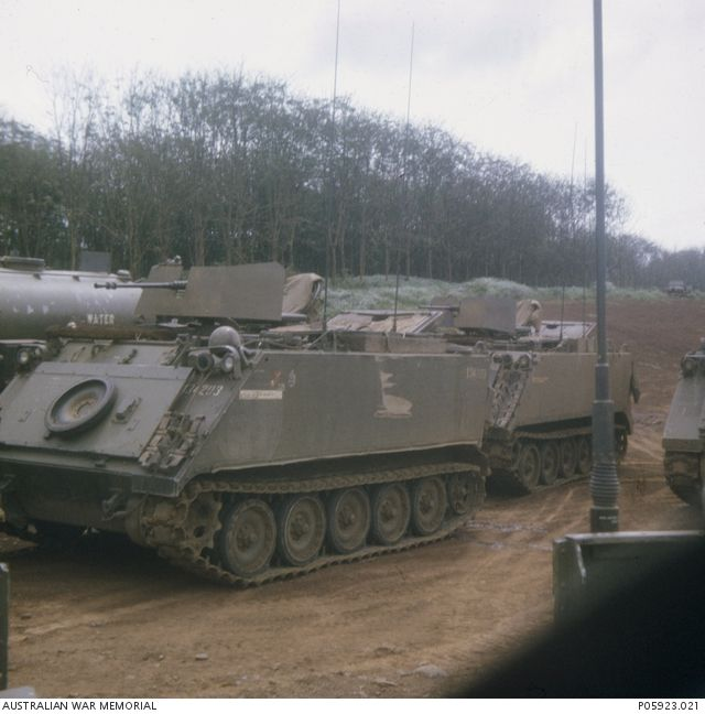 A group of M113A1 Armoured Personnel Carriers and a water tanker (background) at the Petrol Oil and Lubricant  point, Nui Dat.