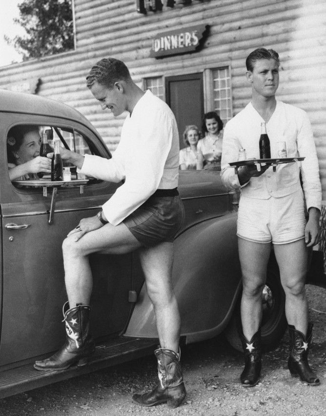 Dallas, 4/27/1940 In this photo from April 27, 1940, dressed in shorts and cowboy boots, carhop Joe Wilcox serves a smiling Pauline Taylor as James Smith heads to serve another car at the drive-in. Bowing to the demands of Dallas women who objected to girl carhops in shorts, one drive-in hired four young men as carhops.