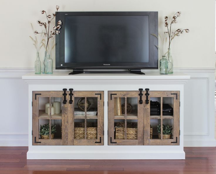 A large farmhouse-style media cabinet with ample storage and shelving on the inside of double 4-pane doors on both sides. Finished with black right angle brackets and surface door latches for added character.