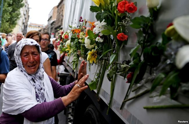 FILE - A woman cries beside a truck carrying 136 coffins of newly identified victims of the 1995 Srebrenica massacre, in front of the presidential building in Sarajevo July 9, 2015.