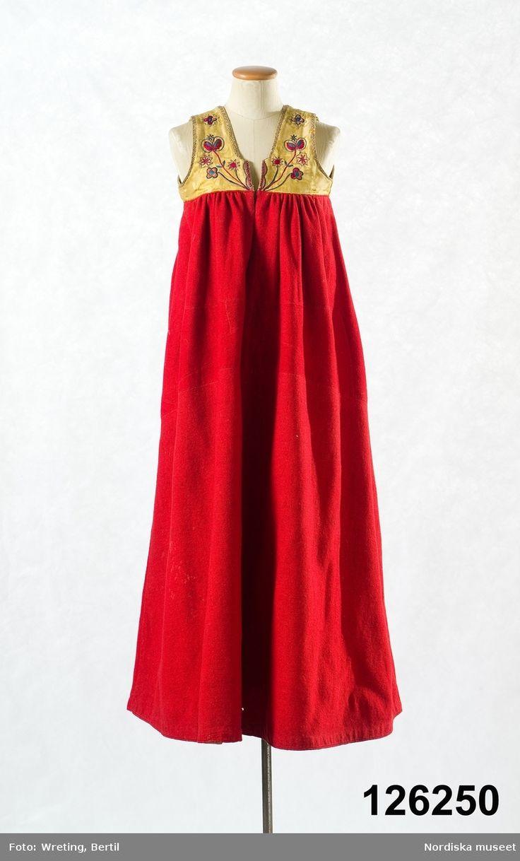 Livkjol med kjol av röd vadmal i 2 våder med kilar infällda nedtill i sidömmarna. Flera materialskar fram dolt under förklädet. Österåker, Södermanland.
