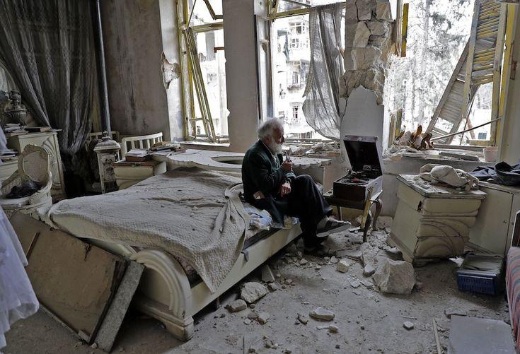 Mohammed Mohiedine Anis, 70 anni, fuma la sua pipa seduto nella sua stanza da letto ad Aleppo mentre ascolta un vinile (JOSEPH EID/AFP/Getty Images)