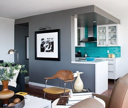 Bold Turquoise Kitchen    Colour blocking delineates the kitchen in an open concept space.      Glossy turquoise subway tiles in the kitchen's backsplash, paired with grey and white walls, amps up the seaside vibe of the space. Excellent color palette