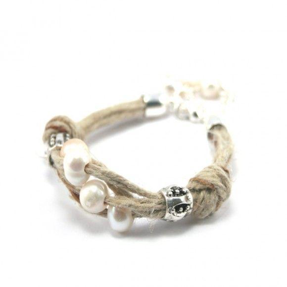 Pulsera de cuerdas de lino en dos colores. Lleva nudos, adornos de metal y perlas. El cierre es de metal con perlas como motivo decorativo.