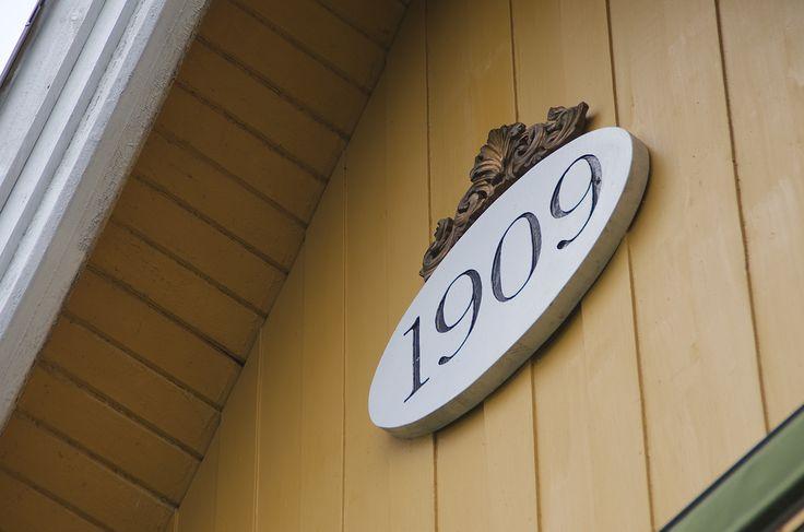 I nabolaget vårt har mange hus byggeåret på fasaden. Skiltet er skåret ut av en benkeplate, tallene er frest inn med overfres og lakkert med svart bengalakk. Utskjæringen er en klokketopp som er sprayet med gullmaling.