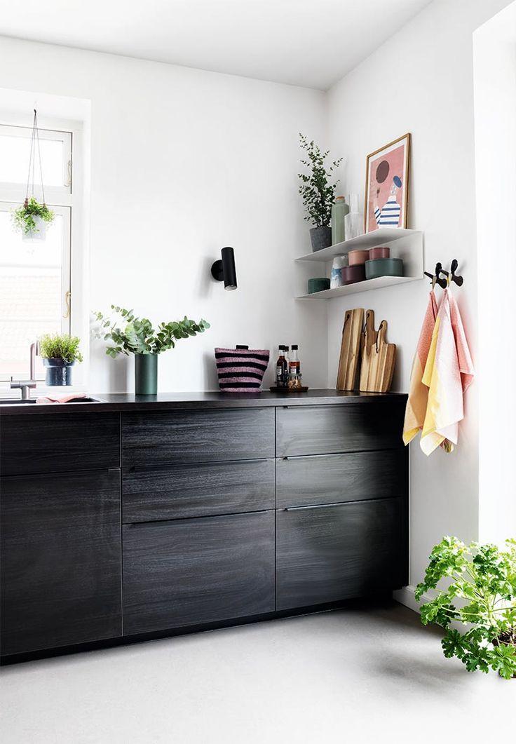 Køkken med sorte elementer i træ med gråt linoleumsgulv og detaljer og pynt i feminine toner