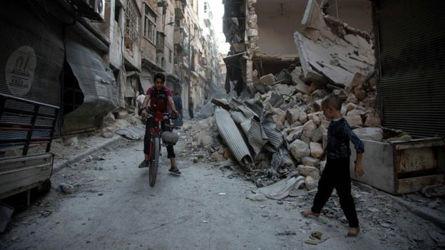 Syrians walk through the rubble