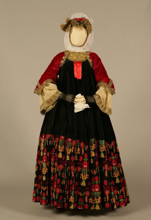 Bridal costume of Skopelos, Sporades  Early 20th century  © Peloponnesian Folklore Foundation, Nafplion, Greece  The bridal costume of Skopelos is called foustána or stófa after the long, richly pleated outer sleeveless dress, which is made of sixteen metres of black silk satin . In earlier times it had a hem of brocade (stófa), which was later replaced by a band of lavish embroidery with the same floral designs.