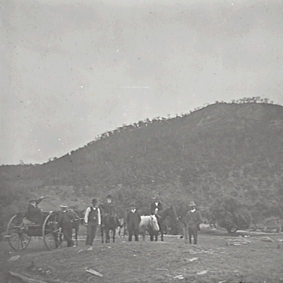 Title: The convict stockade near Mt. Blaxland Date & Location: 27 October 1912, Mount Blaxland (NSW) Description: Black and white glass lantern slide. Title in ink on upper edge label. Notes: Unidentified group of men at the site of a former convict stockade at Mount Blaxland. Man seated in buggy on left gestures towards mountain in background, while others, standing or on horseback, gather around mound in foreground. From negative in Mitchell Library Frank Walker Collection ON 150, Item…