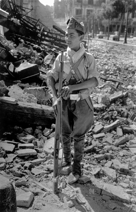 Robert Capa © International Center of Photography View profile SPAIN. Toledo. September 1936. A young Communist militiaman standing near the ruins of the Alcazar.