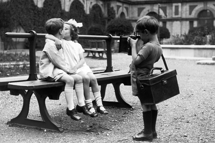 A young photographer capturing a kiss on camera at a children's party at Alexandra Palace, London, 1926.